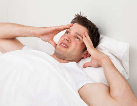 hangover: Young Man Suffering From Headache Lying On Bed Stock Photo