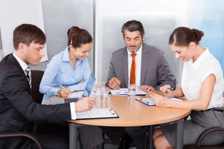 round table conference: Busy Coworkers Working Together At Desk In Office Stock Photo