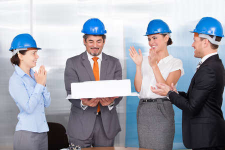 Happy Coworkers Applauding For A Architect Holding Architectural Model photo
