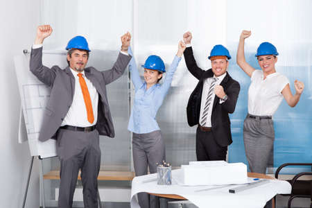 Group Of Architect Wearing Blue Hardhat Expressing Joy At Office photo
