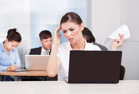 Young Businesswoman Sitting In Front Of Her Colleagues Suffering From Headache photo