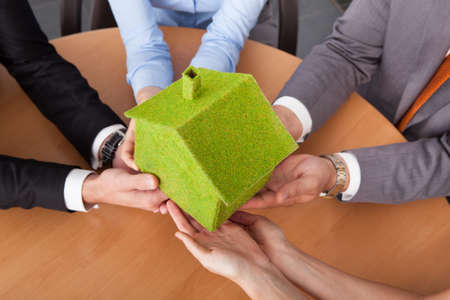 Close-up Of Business People's Hand Holding Eco Friendly Green House Over Desk photo
