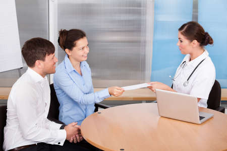 Happy Young Couple Giving Envelope To Female Doctor Stock Photo - 23778042