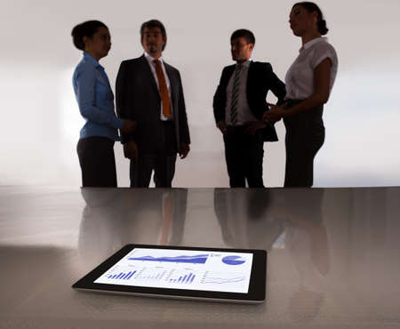 Digital Tablet On Desk In Front Of Businesspeople Discussing Together photo