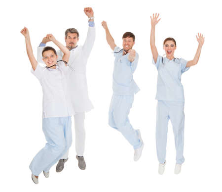 Group Of Doctors Expressing Joy With Raising Hands Over White Background photo