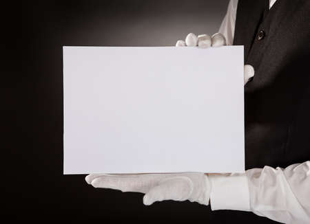 Closeup Of Young Waiter Presenting Blank Placard Over Black Background photo