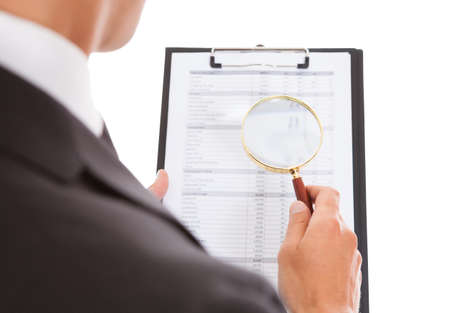 Man Enlarging Content On Clipboard With Magnifying Glass photo