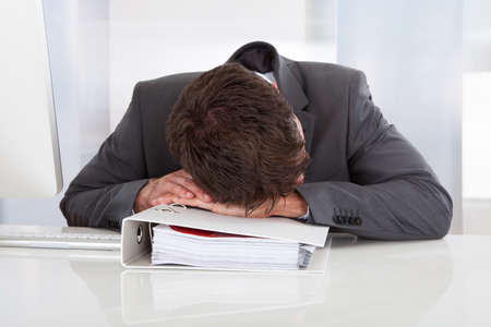 Tired Businessman Sleeping Over Folder At Office photo