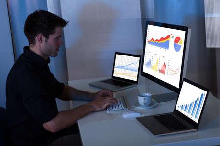 equidad: Hombre joven que trabaja en la computadora en la oficina en la noche