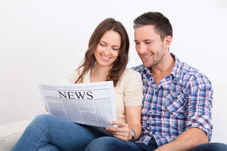 Portrait Of A Happy Young Couple Sitting On Couch Reading Newspaper photo