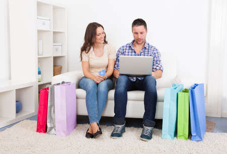 Young Couple Sitting On Couch With Shopping Bags Around photo
