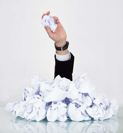 Person Under Pile Of Crumpled Paper With Hand Holding A Paper photo