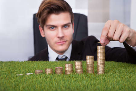office environment: Close-up Of Businessman Stacking Coins Over Grass