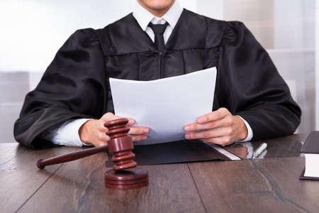 ドキュメントを保持マレットの前で男性裁判官のクローズ アップ 写真素材