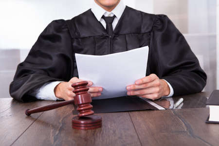 Close-up van mannelijke Rechter Tegenover Mallet Holding Documenten