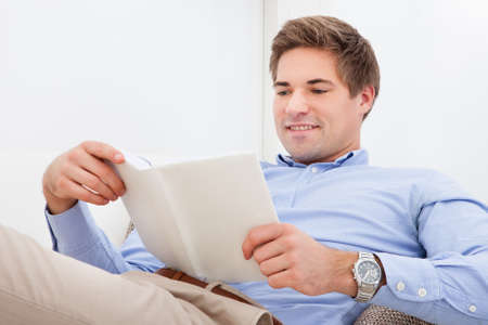 Happy Young Man Sitting On Couch Reading Book photo