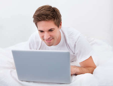 Portrait Of A Young Man Lying On Bed Using Laptop photo