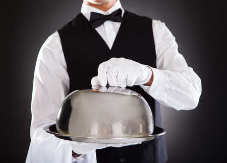 butler: Portrait Of A Male Waiter Holding Tray And Lid Over Black Background Stock Photo