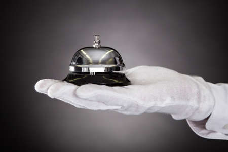 Close-up Of Hand With White Gloves Holding Service Bell photo