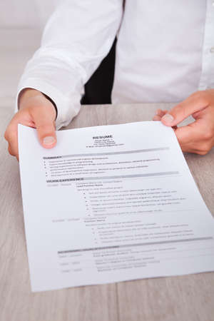 Close-up Of Businessmans Hand Holding Resume On Desk photo