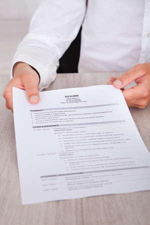 job qualifications: Close-up Of Businessmans Hand Holding Resume On Desk