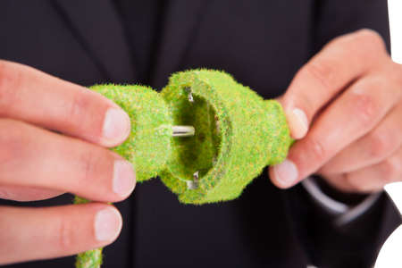 Close-up Of Businessman Hand Holding Grass Covered Electric Plug And Socket photo