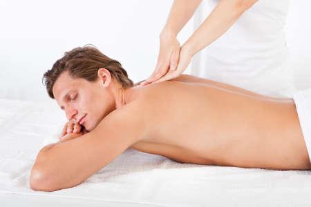sports massage: Hombre descamisado Acostado boca abajo recibiendo tratamiento de spa