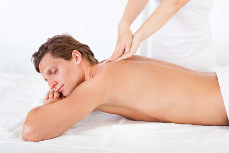 relax massage: Shirtless Man Lying On Front Getting Spa Treatment Stock Photo