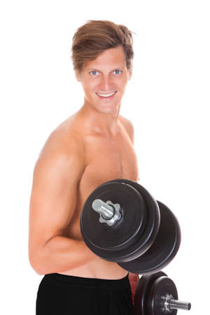Shirtless Man Exercising With Dumbbells Over White Background photo
