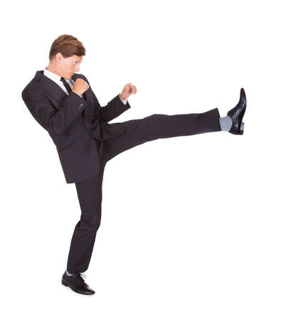 Young Man In Black Suit Kicking On White Background photo