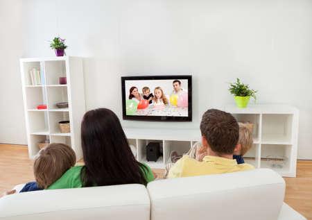 自宅でテレビを見ている若い幸せな家族 写真素材