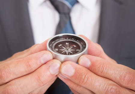 Close-up Of Young Businessman Looking At Compass Stock Photo - 23735140