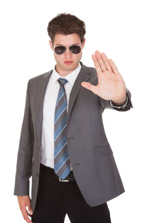 Portrait Of Young Businessman Gesturing On White Background photo