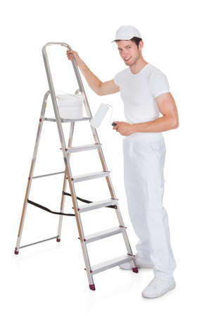 contruction: Happy Painter With Paint Bucket And Roller Standing On Ladder Editorial