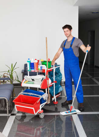 office cleanup: Portrait Of Young Happy Man Standing With Cleaning Equipment In Office Editorial