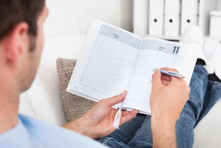 appointment book: Close-up Of A Young Man Sitting On Couch Writing In Diary