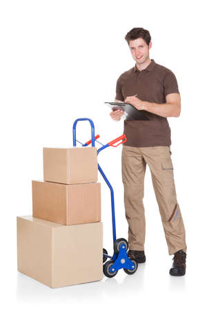 Young Delivery Man Holding Clip Board Standing With Stack Of Boxes Stock Photo - 23735004