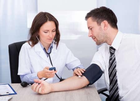 hipertension: Doctora comprobaci�n de la presi�n arterial del hombre de negocios joven