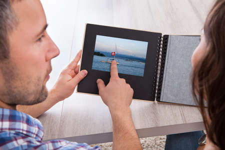 Woman Looking At Photo Album Pointed By Young Man photo