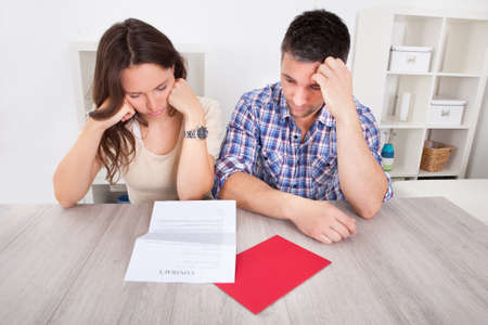 confused woman: Portrait Of A Worried Young Couple Looking At Paper Editorial