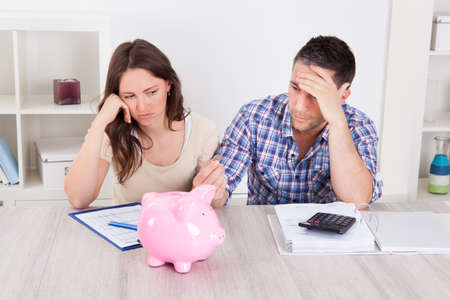 Woman Looking At Piggybank Raised By Young Man Stock Photo