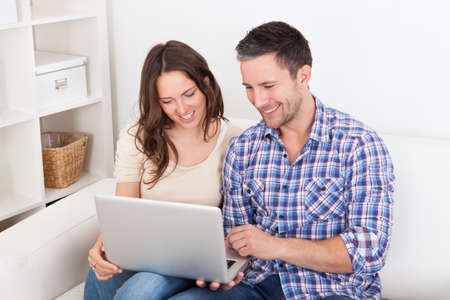 couple couch: Portrait Of A Happy Young Couple Sitting On Couch Using Laptop