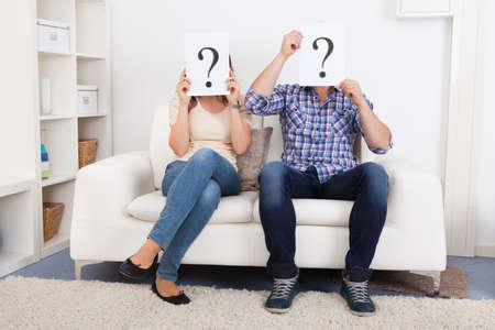 enquiry: Portrait Of Couple Holding Question Mark Sign In Front Of Face