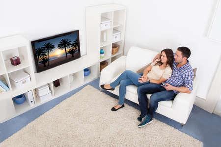 viendo television: Feliz Pareja Joven En Salón Sentado en el sofá viendo la televisión Foto de archivo