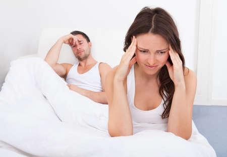 couple au lit: Frustr� femme s'asseyant sur le lit en face de jeune homme