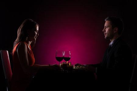 Coppie che hanno cena con vino di vetro sul tavolo