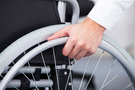 disable: Close-up Of Businessman Sitting On Wheelchair In Office Stock Photo
