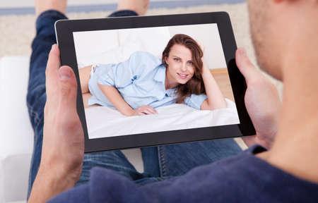 hombros: Primer plano de un hombre hablando por video chats con una mujer joven Foto de archivo
