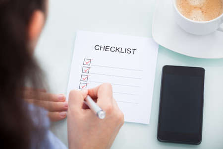 mobile solutions: High Angle View Of A Businesswoman Marking On Checklist At Desk Stock Photo