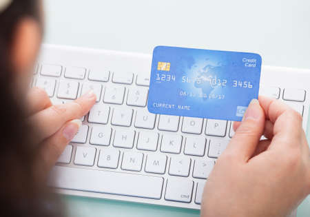 Close-up Of A Person Holding Credit Card Using Laptop